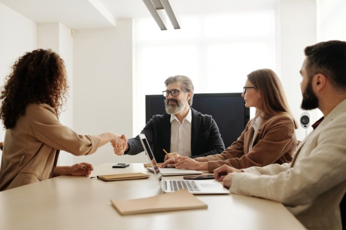 executives around table with new hire to build a better onboarding program
