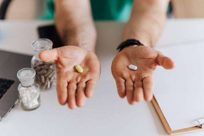 hands holding pills workers comp injury