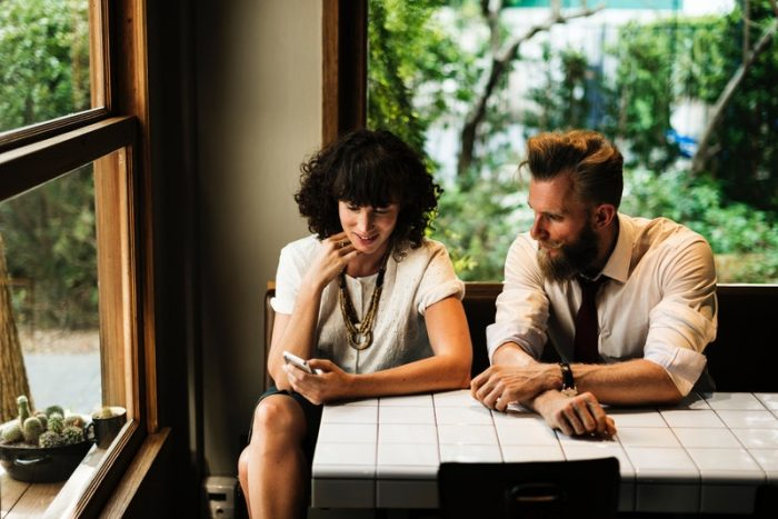 man and woman sitting at table harassment prevention reminder