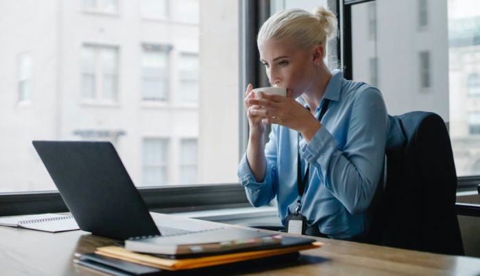 woman taking online training with cup of coffee