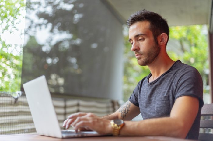 man working on computer reviewing compensation
